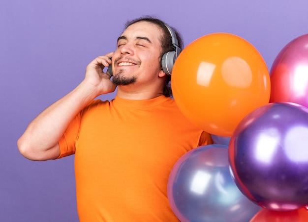 風船の近くに立っているヘッドフォンを身に着けている目を閉じて若い男に満足