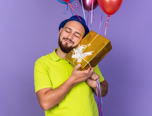 Pleased with closed eyes young man wearing party hat holding balloons with gift box isolated on blue wall
