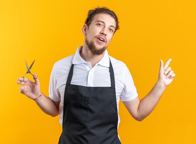 복사 공간 노란색 벽에 고립 된 측면에서 가위 포인트를 들고 유니폼을 입고 머리 젊은 남성 이발사 기울 이기에 만족