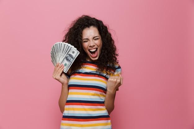 ピンクで隔離されたドルのお金のファンを保持している巻き毛の20代の女性を喜ばせる