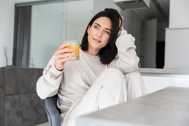 Pleased woman 30s drinking orange juice, while resting in bright modern room