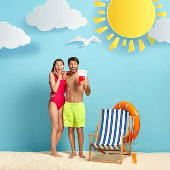 Довольные женщина и мужчина радуются летней поездке, позируют в пляжной одежде с авиабилетами и паспортом, обнимаются и радуются мимике