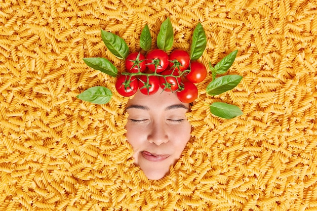 Pleased woman closess eyes licks lips from satisfaction dreams about tasty meal from macaroni surrounded by uncooked pasta red tomatoes and basil leaves above head