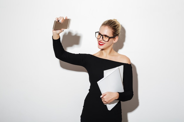 Pleased woman in dress and eyeglasses making selfie on smartphone