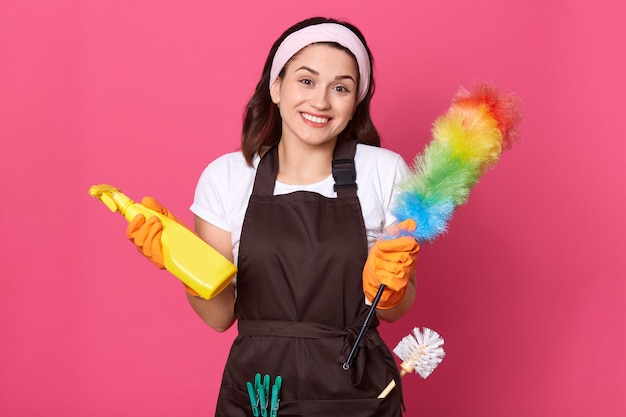 Pleased woman dressed in casual t shirt, apron and hair band, holds detergent and pp duster