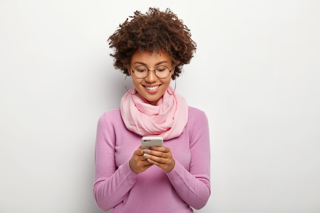 Pleased woman focused in smartphone device, has cheerful expression, checks notification or email box, wears glasses and bright clothes