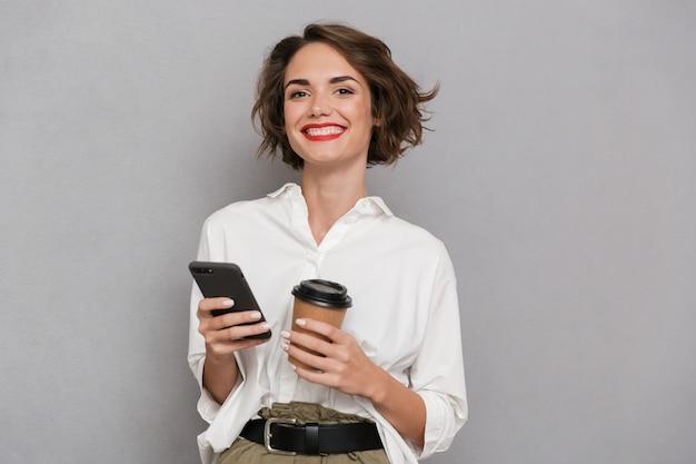 テイクアウトコーヒーを保持し、灰色の壁に隔離された携帯電話を使用して喜んでいる女性
