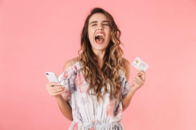 핑크에 고립 된 스마트 폰 및 신용 카드를 들고 드레스에 기쁘게 여자
