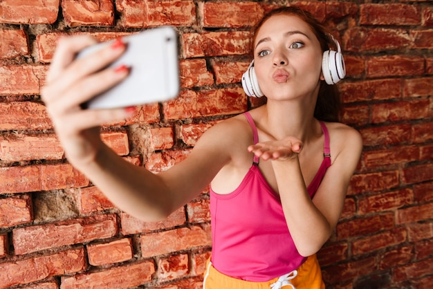 Довольная женщина в наушниках делает селфи на мобильный телефон, отправляя воздушный поцелуй изолированной над кирпичной стеной в помещении