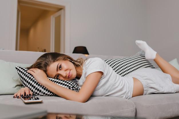 Довольная женщина в носках, лежащая на диване с подушками и нежно улыбаясь