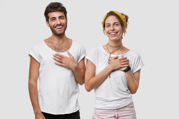 Pleased woman and man keep hands on chest and smile broadly, express gratitude to relatives for help