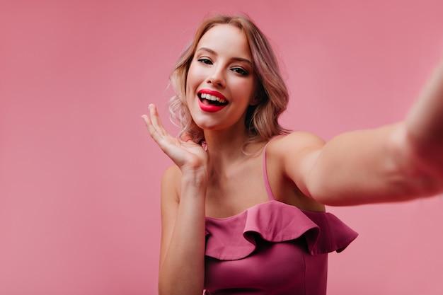 Довольная женщина со светлыми волосами веселится в студии и фотографирует себя