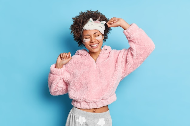 Pleased woman with curly hair dances carefree wakes up early in good mood isolated on blue wall enjoys sleepover at friends house