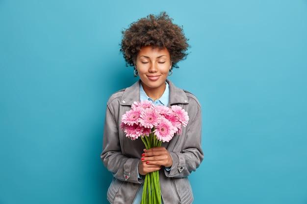 곱슬 머리를 가진 기쁘게 여자는 눈을 감고 유지 아름다운 분홍색 거베라 꽃은 파란색 벽 위에 절연 회색 재킷을 입고 축제 하루를 즐긴다