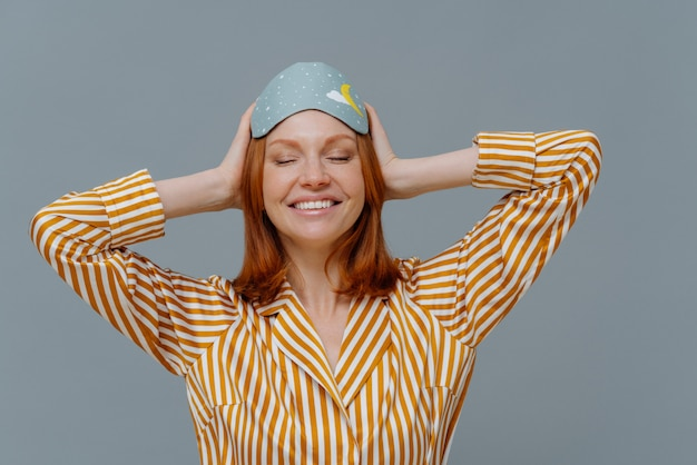 Pleased woman with ginger hair wears comfortable striped pajama and sleep mask