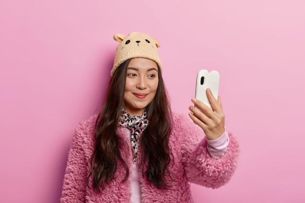 Pleased woman with long hair takes selfie portrait, makes picture on digital device, has long dark hair, photographs herself