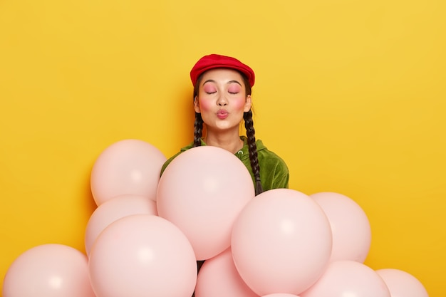 Pleased woman with pink makeup, keeps lips rounded, wants to kiss guests, being thankful for coming on party, stands near balloons, wears fashionable red beret