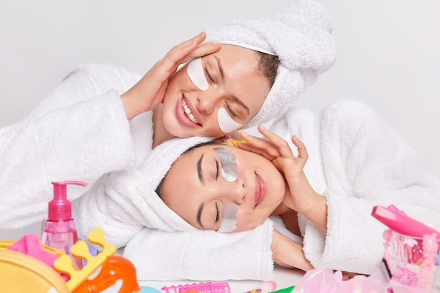 Pleased women take care of facial skin apply patches under eyes to remove puffiness close eyes from satisfaction wear bathrobes towels tilt heads surrounded by different cosmetics isolated