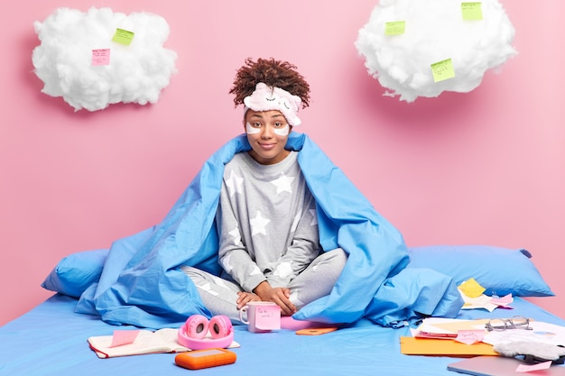 기쁘게 젊은 아프리카 계 미국인 대학생 집에서 침대에서 숙제를