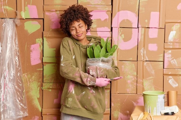 Pleased young african american woman enjoys renovation time at home smeared with paints holds brush potted cactus relocates in new apartment
