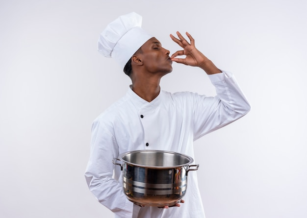 Pleased young afro-american cook in chef uniform holds saucepan and gestures tasty delicious with hand on isolated white background with copy space