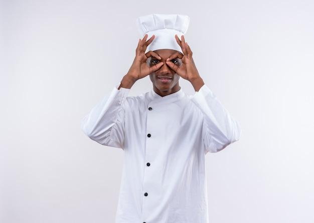 シェフの制服を着た若いアフリカ系アメリカ人の料理人がコピースペースで孤立した白い背景の上の指を見て喜んで