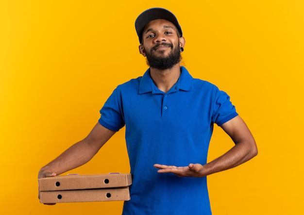 Довольный молодой афро-американский курьер, держащий и указывающий на коробки для пиццы, изолированные на оранжевом фоне с копией пространства