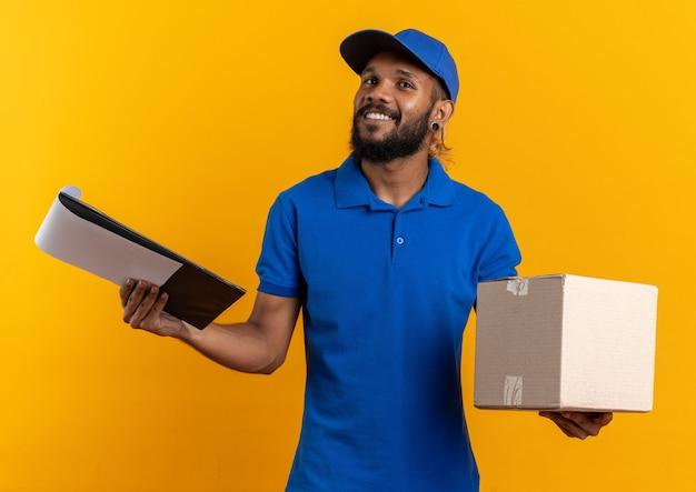 Довольный молодой афро-американский курьер, держащий картонную коробку и буфер обмена, изолированные на оранжевой стене с копией пространства