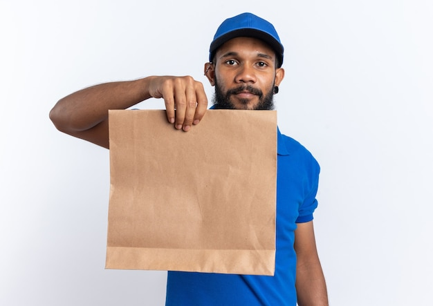 Pleased young afro-american delivery man holding food package isolated on white background with copy space