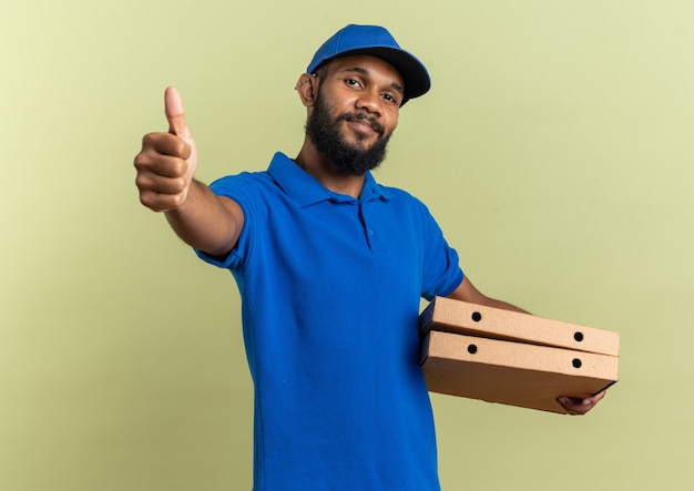 Довольный молодой афро-американский курьер, держащий коробки для пиццы и листающий пальцем вверх, изолирован на оливково-зеленой стене с копией пространства