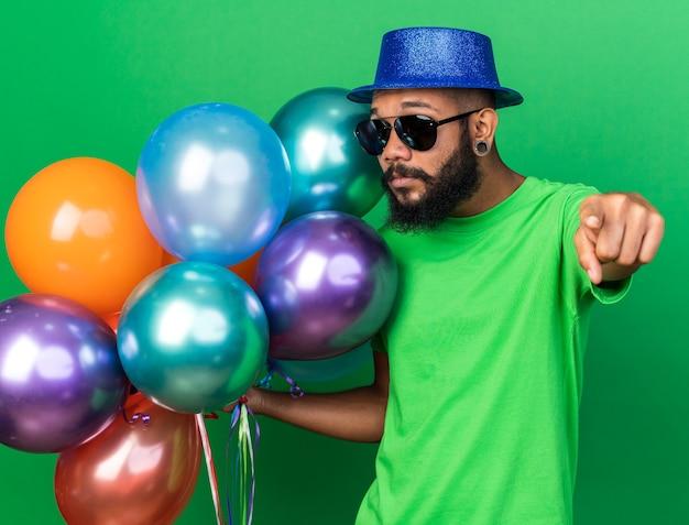 녹색 벽에 격리된 앞에 풍선 포인트를 들고 파티 모자와 안경을 쓴 젊은 아프리카계 미국인 남자