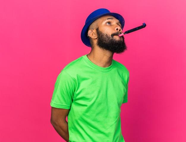 ピンクの壁に分離されたパーティーの笛を吹くパーティーハットを身に着けている若いアフリカ系アメリカ人の男を喜ばせる