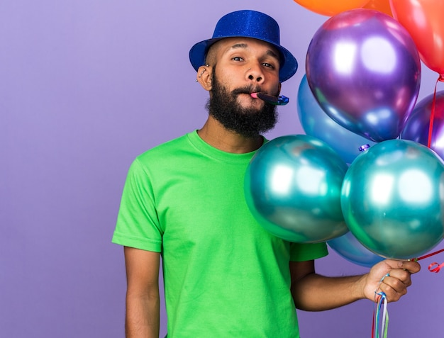 Pleased young afro-american guy wearing party hat holding balloons blowing party whistle isolated on blue wall