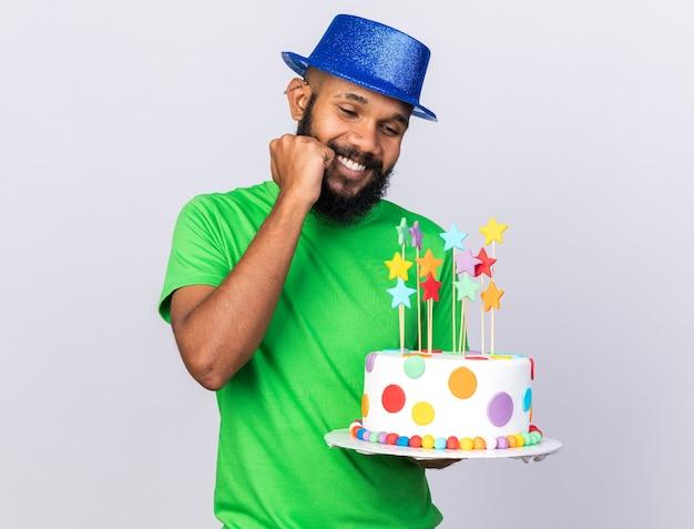Felice giovane ragazzo afro-americano che indossa cappello da festa tenendo la torta mettendo la mano sulla guancia isolata sul muro bianco