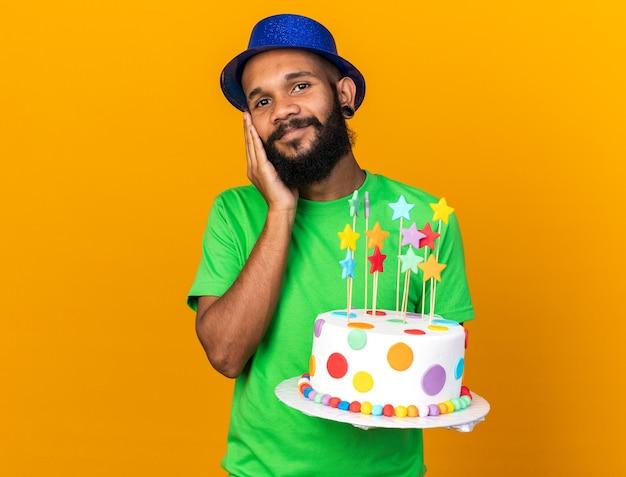 Felice giovane ragazzo afro-americano che indossa un cappello da festa tenendo la torta mettendo la mano sulla guancia