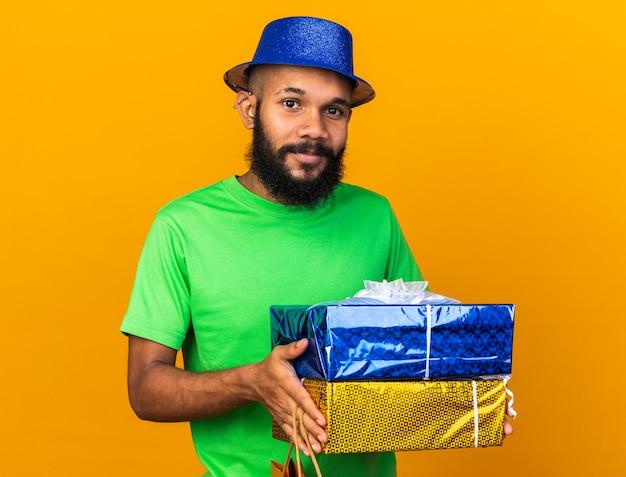 オレンジ色の壁に隔離されたギフトボックスを保持しているパーティーハットを身に着けている若いアフリカ系アメリカ人の男を喜ばせる
