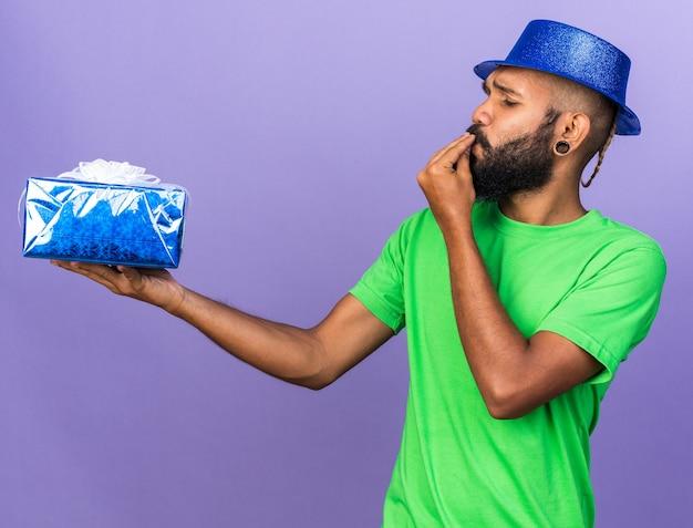 Felice giovane ragazzo afroamericano che indossa un cappello da festa che tiene in mano e guarda una confezione regalo che mostra un gesto delizioso