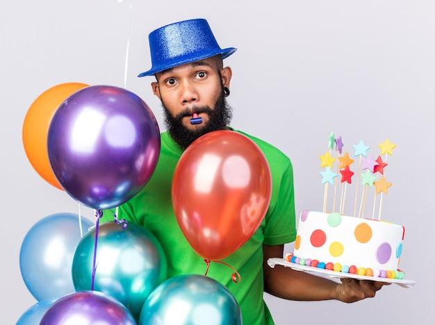 Felice giovane ragazzo afro-americano che indossa un cappello da festa in piedi dietro i palloncini che tengono la torta che soffia fischio di festa isolato sul muro bianco