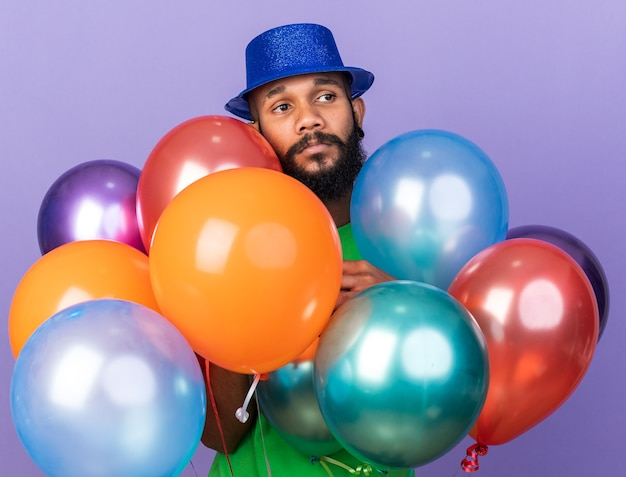 Pleased young afro-american guy wearing party hat standing behind balloons isolated on blue wall