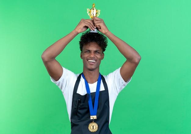 Довольный молодой афро-американский мужчина-парикмахер в униформе и кубке победителя, поднимающий медали, изолирован на зеленом фоне