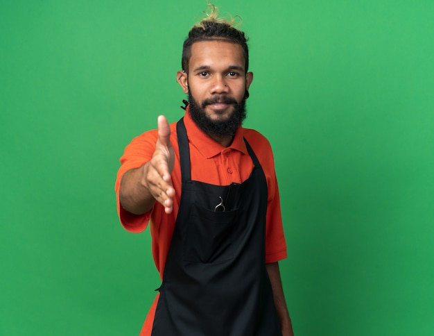 挨拶のジェスチャーをしている制服を着た若いアフリカ系アメリカ人の男性理髪師を喜ばせる