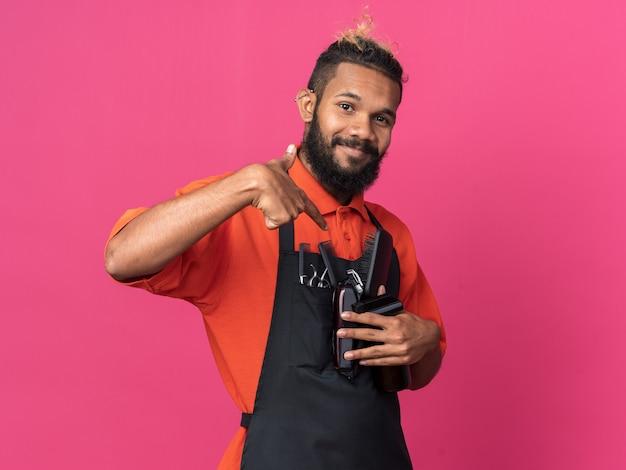 彼らを指している床屋の道具を持っている制服を着ている若いアフリカ系アメリカ人の男性の床屋を喜ばせた