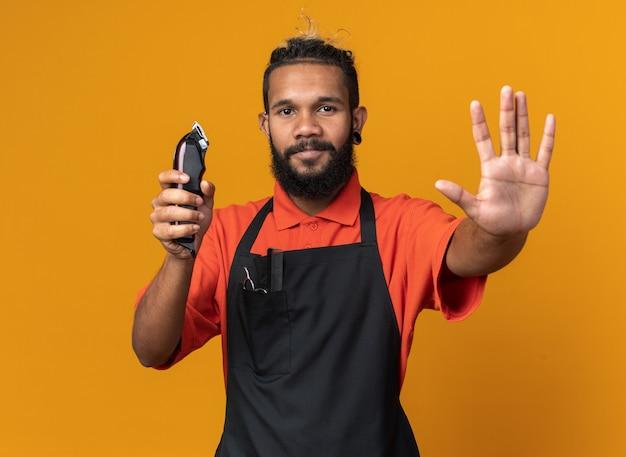 Довольный молодой афро-американский парикмахер в униформе держит машинку для стрижки волос и делает стоп-жест