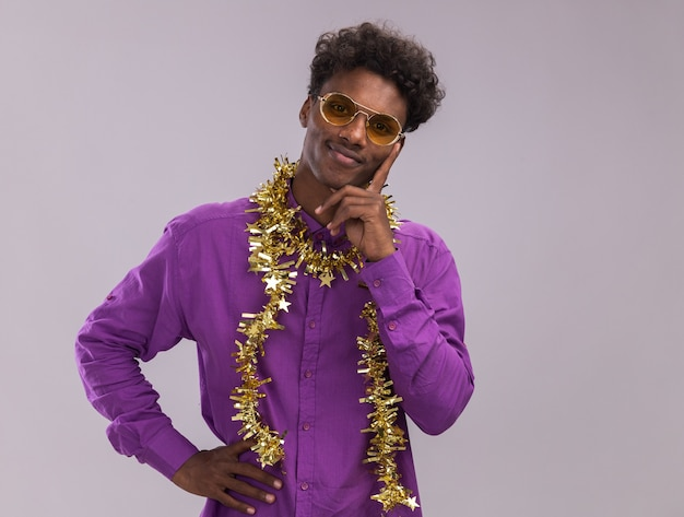 Pleased young afro-american man wearing glasses with tinsel garland around neck looking at camera keeping hand on waist and on chin isolated on white background with copy space