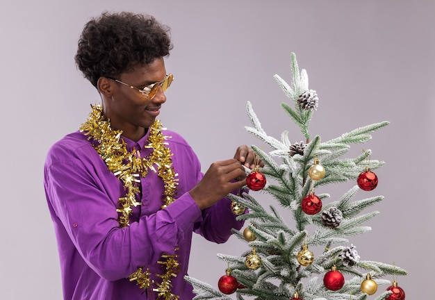 Pleased young afro-american man wearing glasses with tinsel garland around neck standing near christmas tree decorating it with christmas baubles looking at tree isolated on white wall