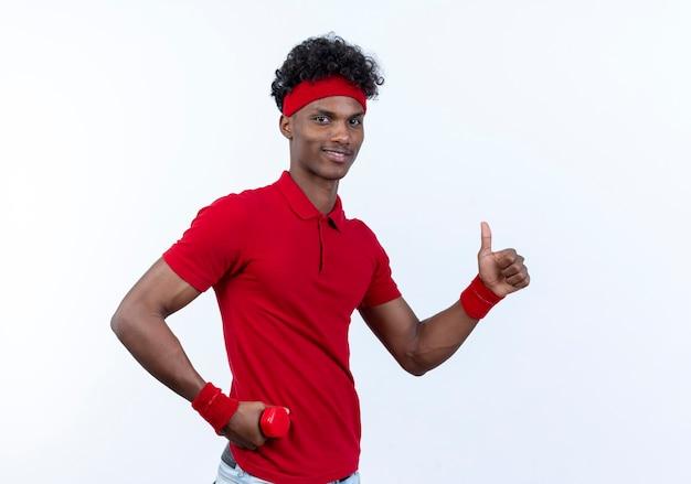 Довольный молодой афро-американский спортивный мужчина с повязкой на голову и браслетом, держащим гантель вокруг бедра, его большой палец вверх изолирован на белом фоне