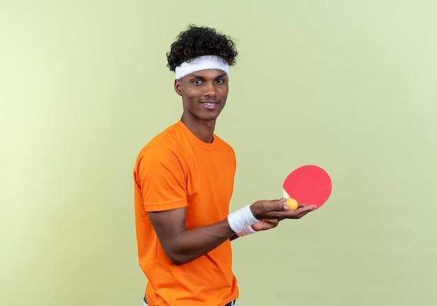 녹색 배경에 고립 된 공을 탁구 라켓을 들고 머리띠와 팔찌를 입고 기쁘게 젊은 아프리카 계 미국인 스포티 한 남자