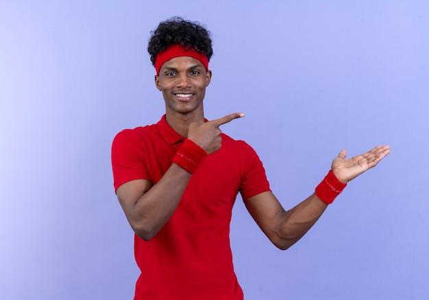 복사 공간이 파란색 벽에 고립 된 측면에 손과 손가락으로 머리띠와 팔찌 포인트를 입고 기쁘게 젊은 아프리카 계 미국인 스포티 한 남자