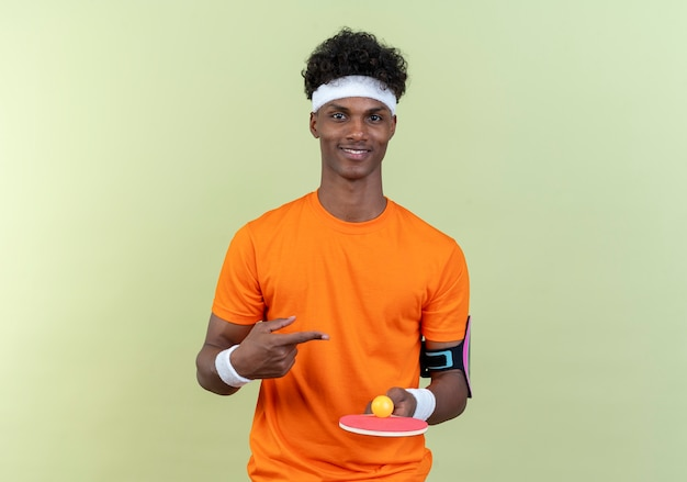 Lieto giovane afro-americano sportivo uomo che indossa la fascia e la tenuta del braccialetto e punti a ping pong racchetta con sfera isolata su sfondo verde