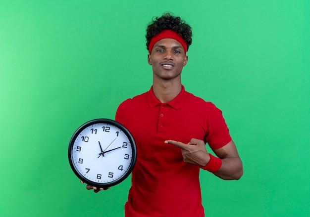 Felice giovane afro-americano sportivo uomo che indossa la fascia e la tenuta del braccialetto e indica l'orologio da parete isolato su sfondo verde